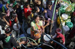 Residents filling their empty containers with water from a municipal tanker in New Delhi, India, today.