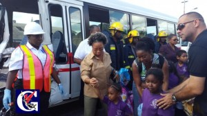 Teachers and officers help the children into the Prison Service bus which took them to the hospital.