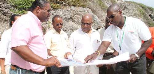 (From left) Project Manager of the Project Coordinating Unit, Sewerage and Solid Waste Ricardo Marshall, Director of the Drainage Division Jason Bowen, Minister of the Environment and Drainage Dr Denis Lowe and Acting Director of Coastal Zone in the Ministry of the Environment Antonio Rowe examining a plan as they tour Crane Beach.