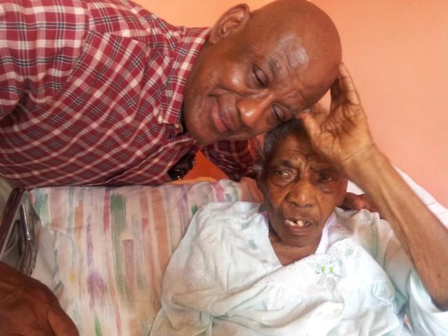 Centenarian Muriel Greenidge being shown  some affection by her great-nephew Calvin Smith.