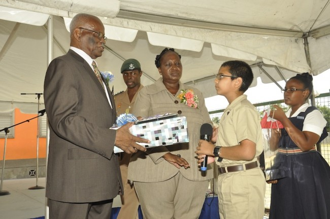 Governor General Sir Elliott Belgrave (at left) accepting a gift from Westbury Primary head boy Zakariyya Nana (second from right). Looking on is aide-de-camp Captain Carlos Lovell (second from left), principal Rosalind Gittens (third from left) and deputy head girl Leeann Clarke.