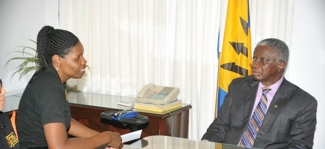 Prime Minister Freundel Stuart listening attentively to President of the Barbados Council For The Disabled, Maria Holder-Small.