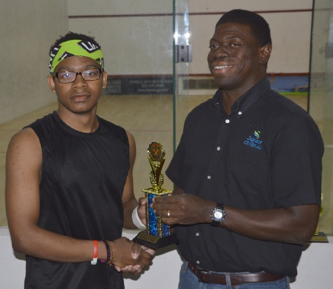 Under-19 champion Benjamin Griffith (left) accepts his trophy from Roger Spencer of Sagicor General Insurance.(BB)
