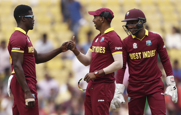 West Indies' Samuel Badree, center, celebrates with teammates the wicket of Afghanistan's Mohammad Shahzad during their ICC World Twenty20 2016 cricket match in Nagpur, India, Sunday, March 27, 2016. (AP Photo/Saurabh Das)