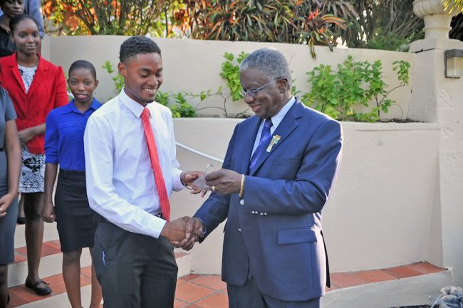 Prime Minister Freundel Stuart (right) presenting a commemorative 50th anniversary of Independence pin to President of the Guild of Students of the University of the West Indies, Olvine Holas.