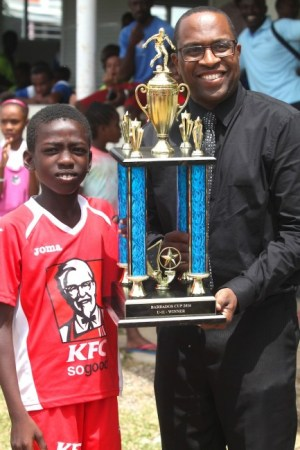 Deputy director of sports at the National Sports Council, Neil Murrell, presented  Under-11 Barbados Cup champions KFC Pinelands with their trophy.