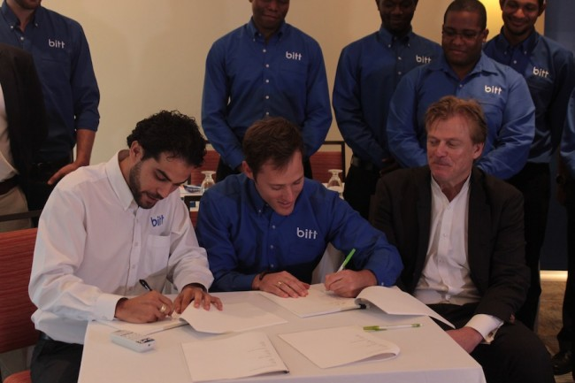Founders of BITT.Com Gabriel Abed (left) and Oliver Gale (centre) signing the deal with investor  Dr Patrick Byrne (right).