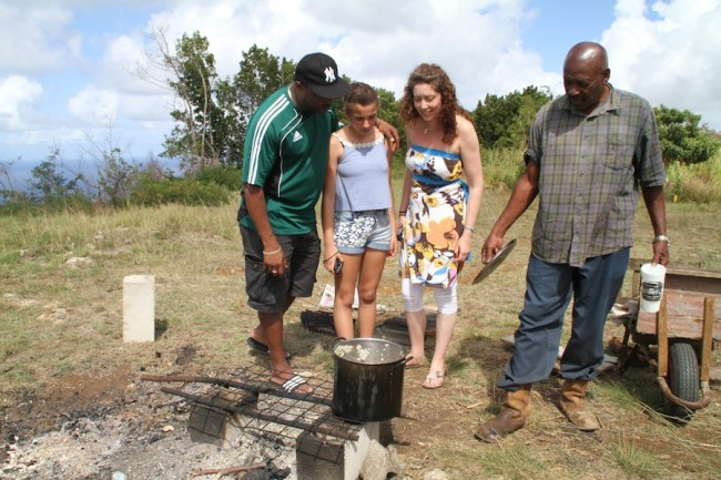 Ovid Sargeant (right) showing Ian Jones (left), his daughter Milly and wife Denise a pot of lentil peas rice and chicken cooked on the outdoors at Hackleton's Cliff.