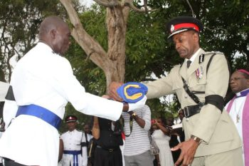 Acting Police Commissioner Tyrone Griffith receives the flag which was draped over the casket.