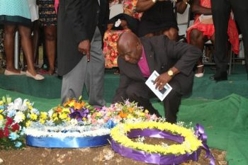 Here, a tearful Reverend Scoffield Eversley lays a wreath on his cousin's grave.
