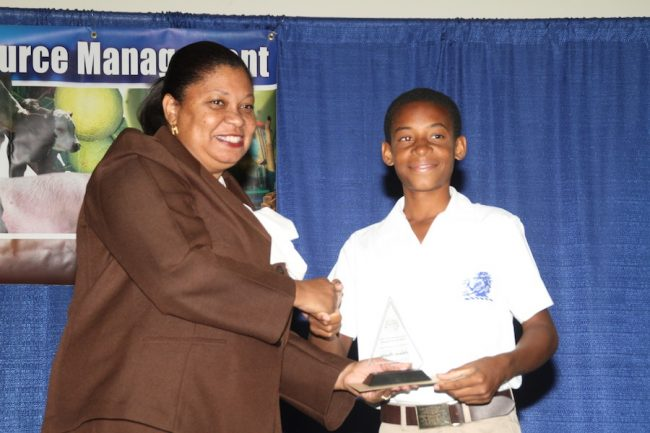 Jelani Hunte (at right), of the Lodge School that captured the Grow Well title, accepting the prize from an official.