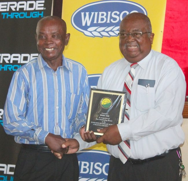Well known track and field starter Basil Cox (left) who worked at the National Stadium for 35 years was recognized for his invaluable contribution to the sport over the years, here he receives an award from principal of The Lodge School Vasco Dash.