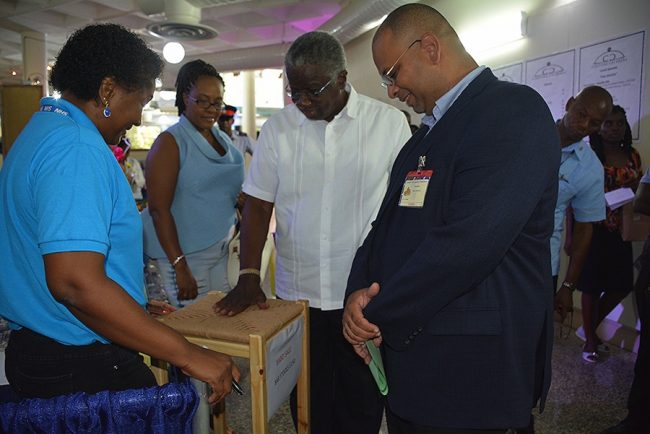 Prime Minister Freundel Stuart checks out a 'rush' covered stool of the Blind and Deaf Association. At right is BMA President Jason Sambrano.
