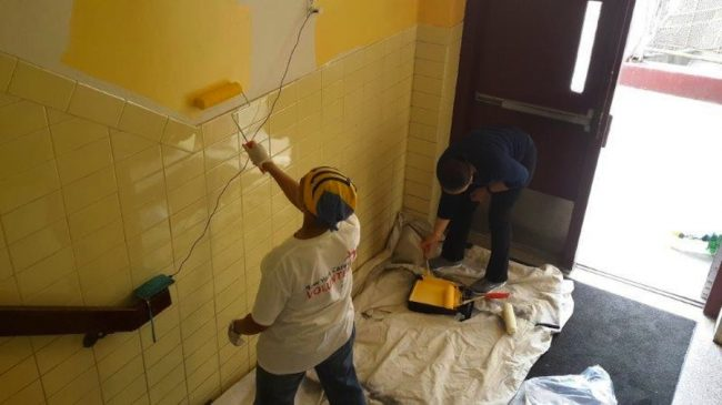 Staffer of the Barbados Consulate in New York and member of the Disapora painting the Nazareth High School.
