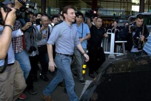 BBC's journalist Rupert Wingfield-Hayes (centre) walks past journalists as he arrives at the airport in Beijing, China on Monday.