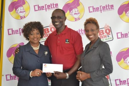 Chefette advertising manager Lisa Carter presenting cheque to Adrian Agard,Gospelfest executive director.