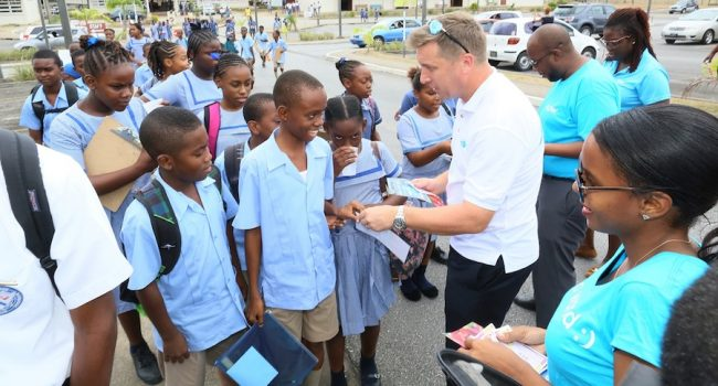 Niall Sheehy, managing director of Flow Barbados, presenting some of the students outside Queen's College with their vouchers.