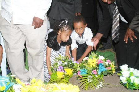 Two of Colin Forde's younger relatives place a wreath at his gravesite.