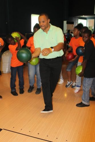 Minister of Finance Chris Sinckler enjoying a game of bowling with some of the children of Eagle Hall Primary School.