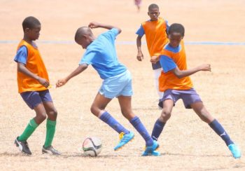 Joshua Kellman of St Luke's Brighton Primary (center) skilfully pulls the ball back while  trying to dribble past Reynold Weekes' defence.