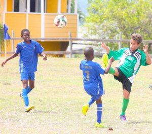 Matteo Batson delivers a chest- high kick to clear the ball away from Shakur Bishop (centre) of St Bartholomew's Primary.
