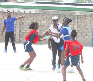 (From left) Deacons Primary goal-attack Caria Smith and Hindsbury goal-defender Ciara Edwards battle for a toss up of the ball while National Sports Council coach Monette Wharton looks on closely.