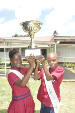 Top students Christina Watson and Trimaine Greaves holding up the Gordon Greenidge Challenge Trophy for the year 2015-2016.
