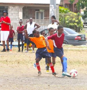 Daniel Best of Gordon Greenidge dribbles past Roland Edwards Primary defenders on his way to the goal bars for one of three goals in the game.