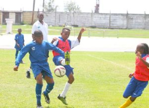 Edwin Barnett (left) of Wesley Hall Primary tries to prevent Kadane Archer of Deacons Primary from pushing the ball forward.