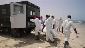 Emergency services remove the body of a victim as more than 100 bodies are pulled from the sea near the western city of Zwara, Libya, on Friday.