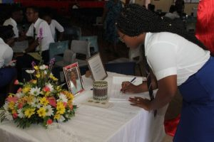 Shermona Rodney, a recent Queen's College graduate, signing the condolence book.