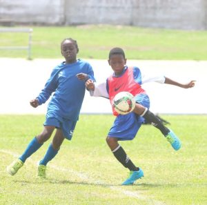 Nathan Gibbs of Deacons Primary tries to clear the ball away from Robinho Husbands of Wesley Hall.