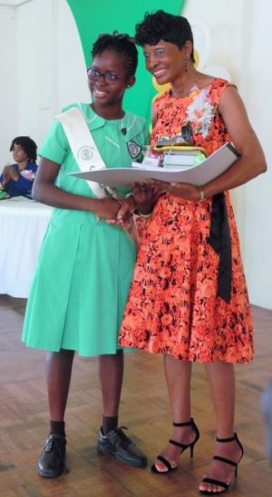 Valedictorian Elena Scantlebury receiving her  prize from  former teacher Yvonne Greene.
