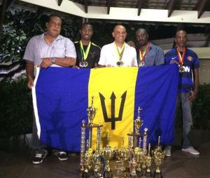 (From left) President of the Barbados Rifle Association Michael Hinkson, Jamar Eastmond, Adrian Marshall, regional director Kevin Grant and Richard Durant show off their shooting trophies.