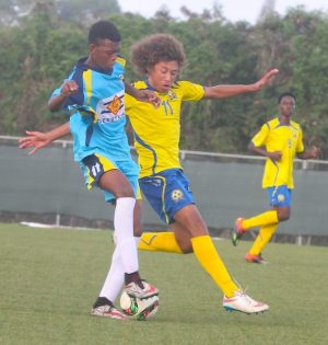 Djal Augustin (left) of St Lucia cuts the ball back and away from Barbadian forward Nigel Griffith.