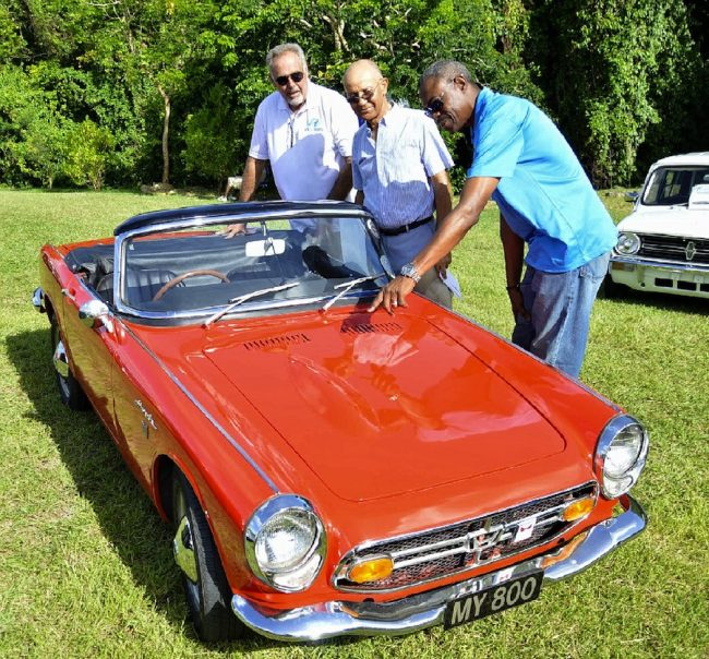 "This 1967 Honda owned by Dr Charles Edwards (centre) was voted ""Car Of The Show"". Here, President of Sagicor General David Alleyne (right) and Phillip Bynoe of Courtesy Garage admire the vehicle."