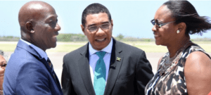 Prime Minister of Trinidad and Tobago Dr Keith Rowley (left) greets Juliet Holness, wife of Jamaica's Prime Minister Andrew Holness (centre) on his arrival Sunday at the Norman Manley International Airport for a four-day official visit.