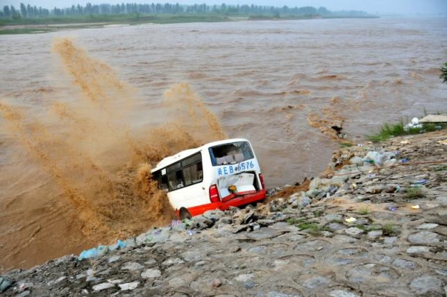 An abandoned bus filled with sand bags is used to build a makeshift dike at a flooded area in Xingtai, Hebei Province, China, July 21, 2016. REUTERS/Stringer