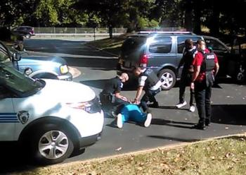 In this image taken from video recorded by Keith Lamont Scott's wife, Rakeyia Scott, on Tuesday, Charlotte police squat next to Keith Lamont Scott as Scott lies face-down on the ground, in Charlotte, North Carolina.