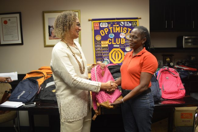 President of the Optimist Club of Bridgetown Lady Carol Haynes (left) handing Principal of Arthur Smith Primary Jennifer Hoyte with one of the bags the Club donated to her school.
