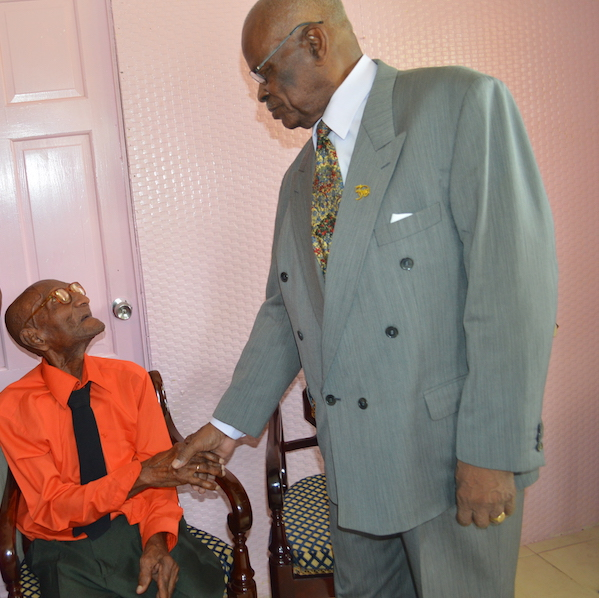Governor General Sir Elliott Belgrave greets centenarian Clement Holdipp.