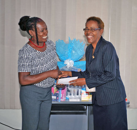 President of the Family Care Support Group, Kedelyn Morgan (left) receiving the cash donation from Administrative Officer and HIV Coordinator in the Office of the Attorney General, Cheryl Grogan.