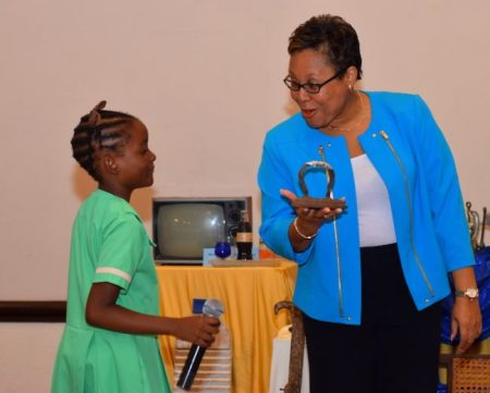 CEO of the Small Business Association Lynette Holder showing an old Barbadian iron to an eager young student of the All Saints Primary School.