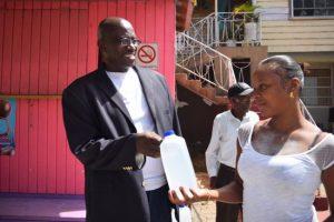 "Here, evangelist Courtney Selman (left) gives Burke's  Village  resident Lisa Grant a bottle of ""blessed"" water."