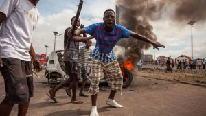 Demonstrators gather in front of a burning car during an opposition rally in Kinshasa.