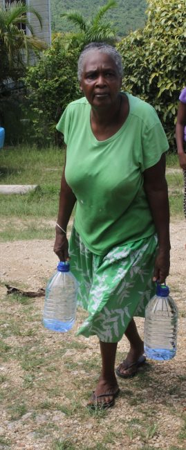 This happy resident  makes her way home with two precious bottles of water.