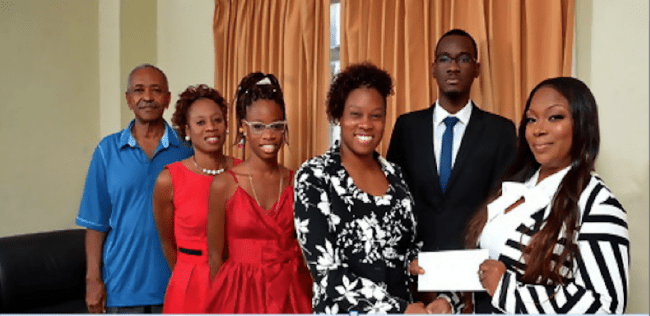 Najla Ahele Rosonia King (fourth left) receives a cheque from attorney-at-law at George Walton Payne & Co and the firm's representative on the Board of Trustees Shontelle Murrell-Hinkson (right), as (from left) Secretary-Treasurer of the Trust Darwin Goodridge, her mother Rosemary King, sister Kyalamboka King-Bruce, and 2015 Scholarship winner Traimaine Taylor look on.