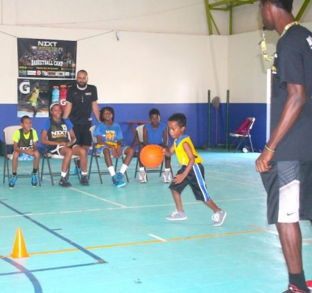 Six-year-old Seth Playter showing off his dribbling skills to the delight of coach Zahir Motara and campers of Next Generation Athletics and Basketball Academy.