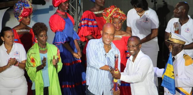 President of Haiti, Michel Martelly hands over the CARIFESTA baton to Culture Minister Stephen Lashley at the close of last year's spectacular festival staged in Port au Prince.