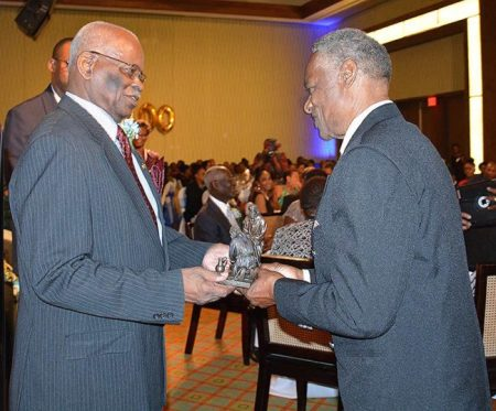 Governor General Sir Elliott Belgrave presents the Lydia Dowdye-Mings Servanthood Award to Dr George Callender.
